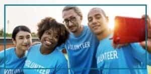 group of volunteers in blue shirts smiling in selfie photo